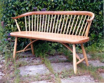 Oak bench with bent back.